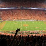 Clemson stadium with thousands of people cheering for a football game.