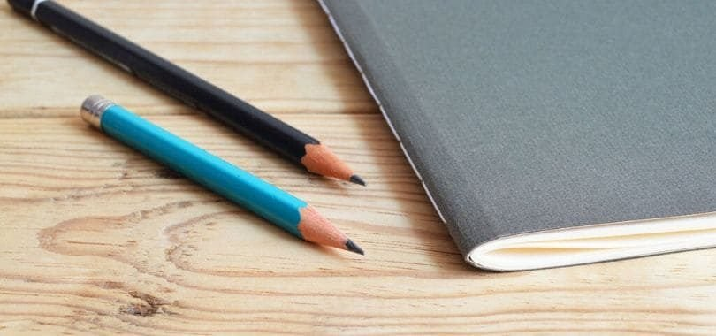 Two pencils laying next to a gray notebook.