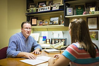 A professor talking to a student in their office.