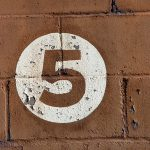 Number 5 on a brick wall.
