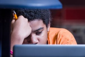 A student intently studying on his laptop while holding a pencil.