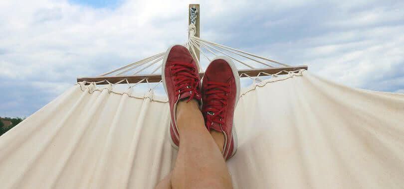 A student relaxing on a hammock wearing red sneakers.
