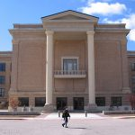 Student walking infront of West Texas A&M University old main building.
