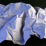 Crumpled piece of paper on a black background.