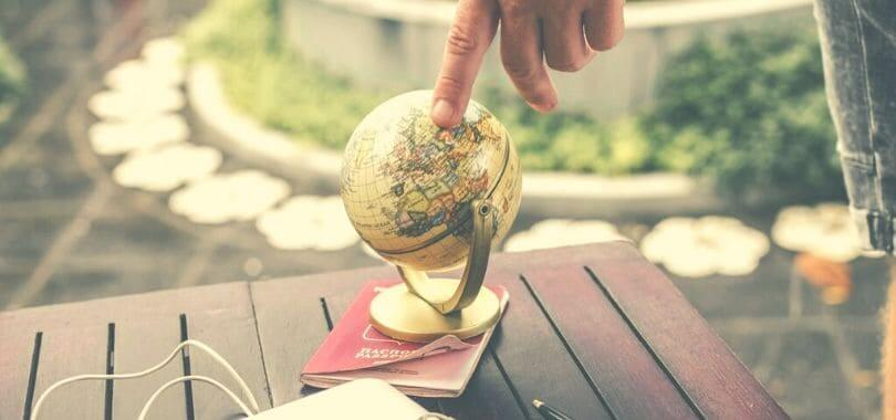 A small globe on top of a passport.