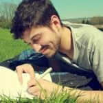 A student lying on a lawn writing down notes on a notebook.