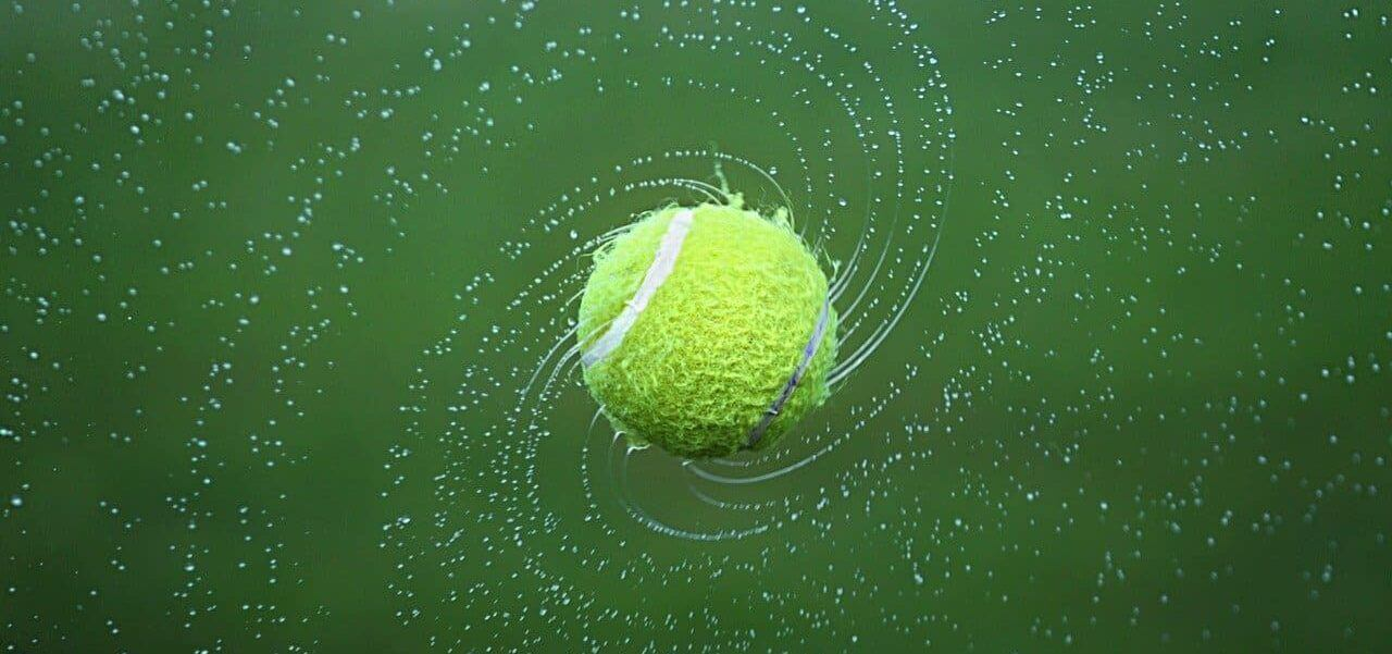 A tennis ball spinning with a darker green background.