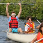 Camp counsellor holding oar above his head guiding children in kayaks on a lake.