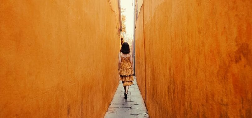 A person walking down a narrow alleyway.