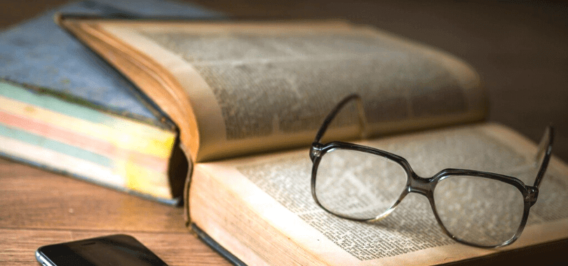 An open textbook with a pair of glasses resting on top of the pages.