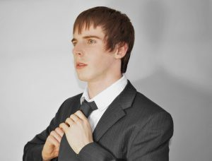 A man fixing his necktie while looking away.