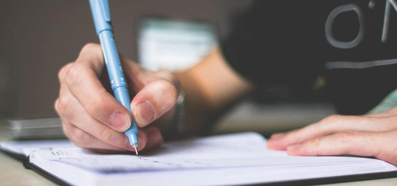 A student holding a pen and writing on a notebook.