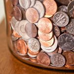 A jar of coins, mostly pennies and dimes.