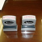 Two grey stampers, one says Approved, the other says Denied.
