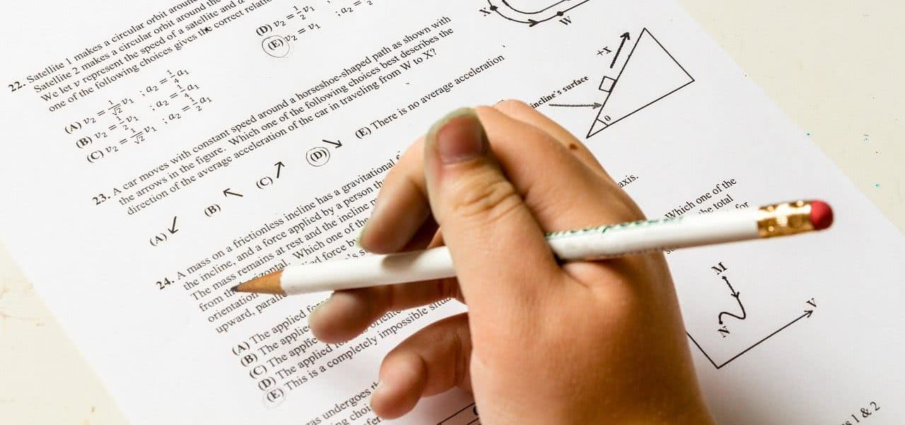 A student holding a pencil over a test sheet.
