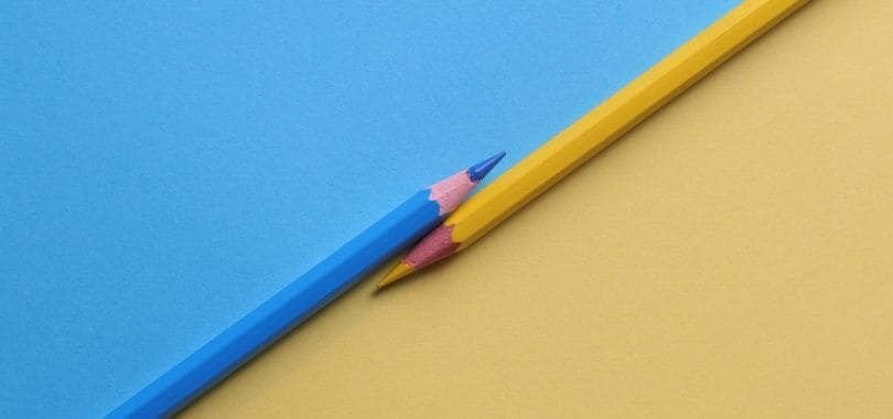 A blue and yellow pencil parallel to each other, with a blue and yellow background.