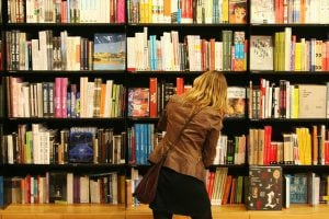 girl checking books on a shelf