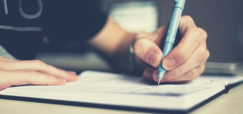 A student holding a pen to a notebook, studying.