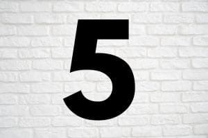 The number 5 against a white brick background.