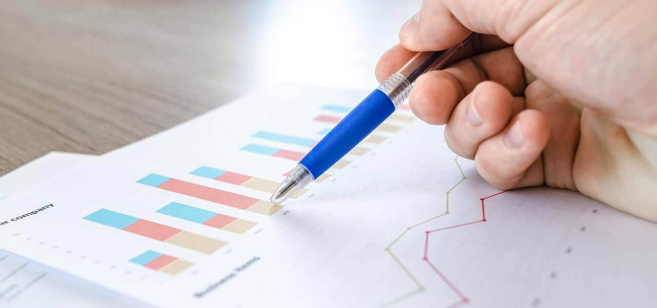 A person holding a pen on top of a printed bar graph.