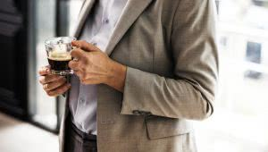 A man wearing corporate suit holding a hot cup of coffee, shown from shoulder to waist.