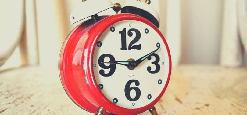 A red alarm clock with black numbers and white alarm bell.