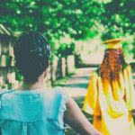 A mother watches her graduating daughter walk down a road.