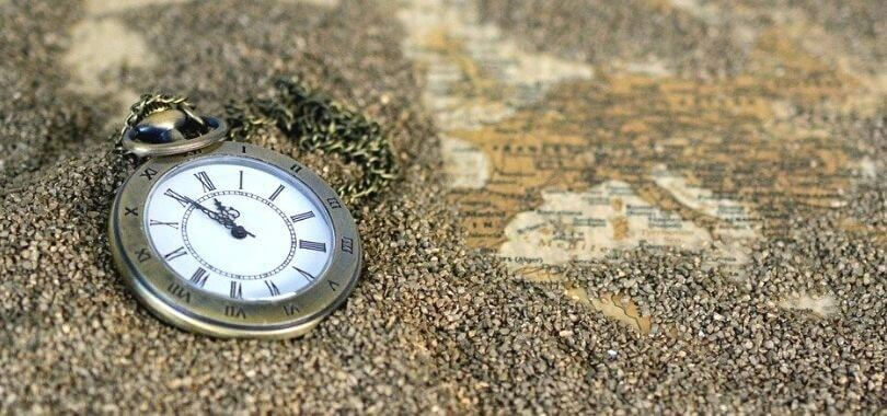A pocket watch laying in sand on a map.