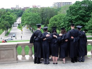 Back view of graduate students hugging each other.