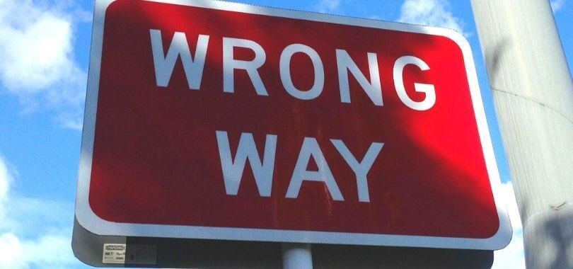 "A red sign with white lettering that says ""wrong way."""