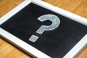 A question mark written in a small chalkboard that is lying on the floor.