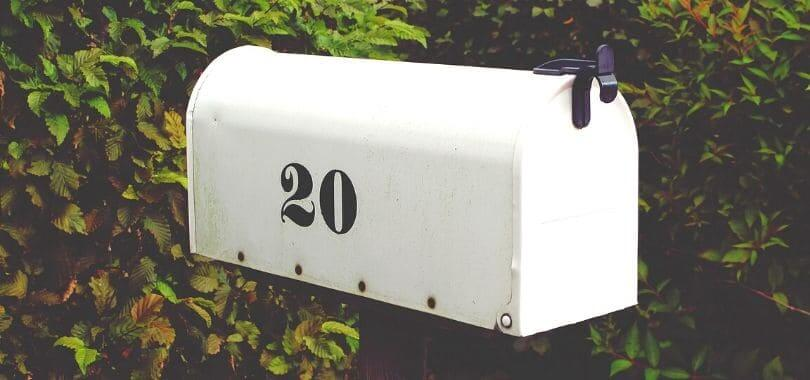 """A white mailbox with """"20"""" printed on the side."""