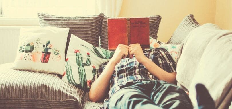 A student reclining on a couch with a book in front of their face.
