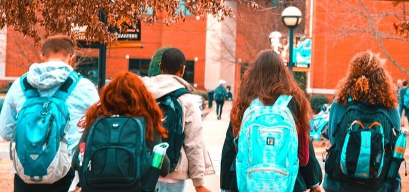 A group of students wearing backpacks walking together.