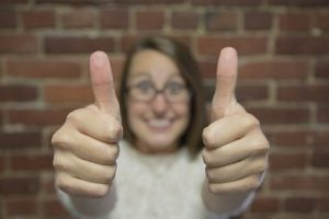 Girl with eye glasses with a big smile while showing two thumbs up.