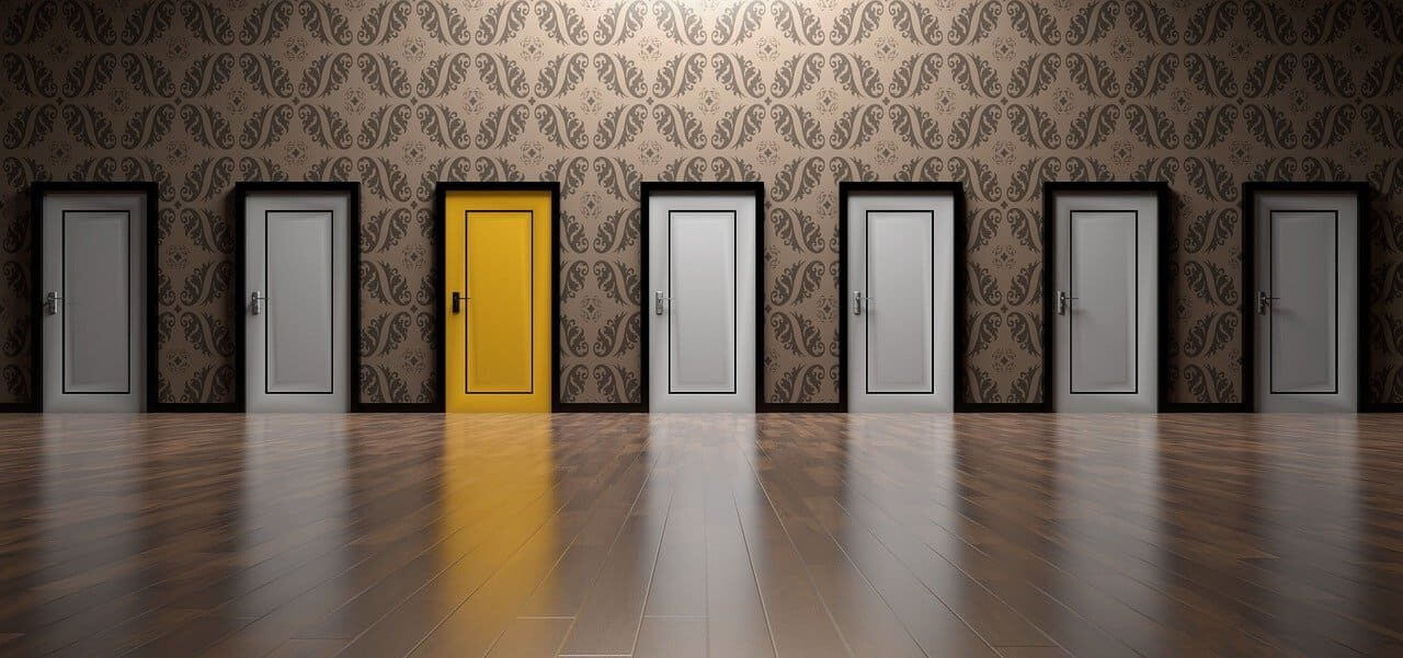 A row of gray doors with one yellow door.
