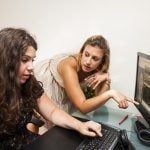 Two girls discussing infront of the computer.