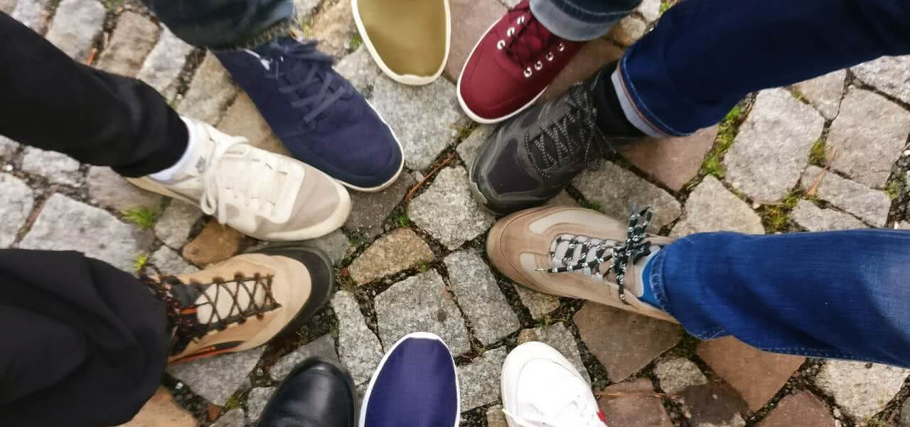Students putting their shoes together in a circle.