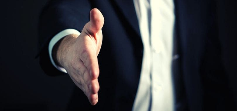 A business person offering a handshake.