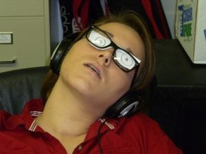 A guy sleeping while wearing eye glasses with doodles on it.
