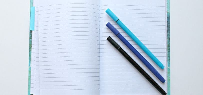 An open notebook with three pens on top of it.