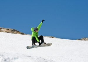 A man wearing a green coat is snowboarding in mid-air.