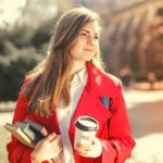 A student wearing a red blazer, holding a cup of coffee and books.