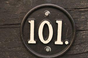 101 number in circular steel and is attached to wood.