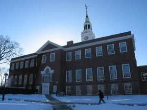 Student walking in front of Dartmouth College campus building with snow-covered lawn.