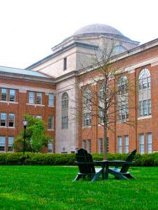 A lawn with a table and two chairs in front of a Davidson College campus building.