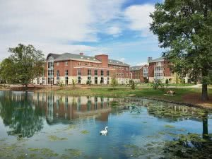Elon University building with a swan in the lake foreground.
