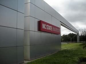 Red NC State University name sign on the outside of a silver building