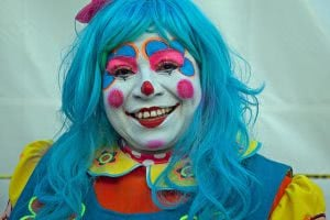 Portrait of a smiling and colorful girl clown.