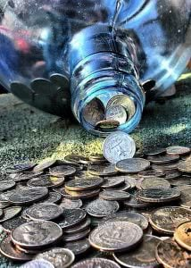 Coins are spilling from a glass jar.